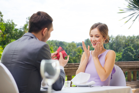 man showing woman present in red box at restaurant Banco de Imagens