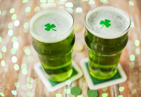 glasses of green beer with shamrock and gold coins