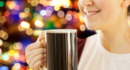 close up of smiling woman with dark beer in mug