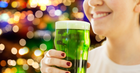 close up of woman with green beer in glass