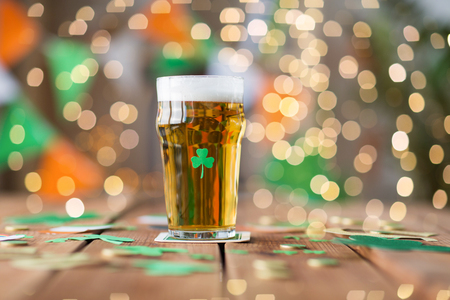 glass of beer with shamrock and coins on table