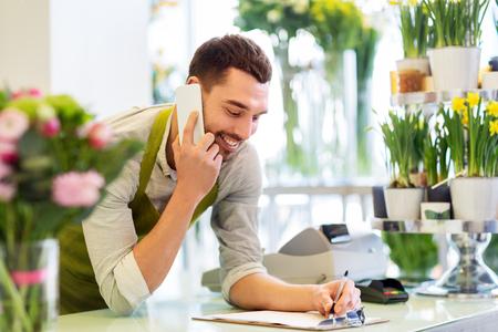 Blumenhändler, der im Blumenladen Smartphone anruft