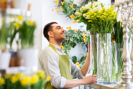 happy florist man setting flowers at flower shop