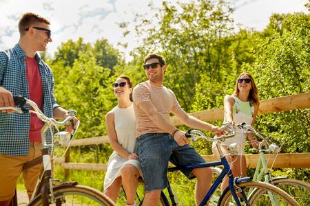 amici felici in sella a biciclette a scatto fisso in estate Archivio Fotografico