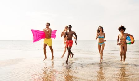 friends run with beach ball and swimming mattress 版權商用圖片 - 115184596