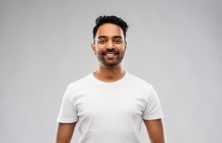 lachende jonge Indiase man over grijze achtergrond Stockfoto