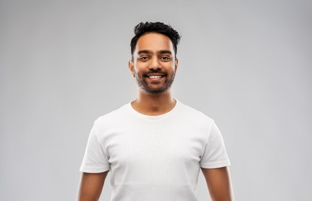 smiling young indian man over gray background