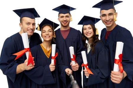 graduados felices con diplomas tomando selfie Foto de archivo