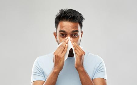 indischer Mann mit Papierserviette bläst Nase