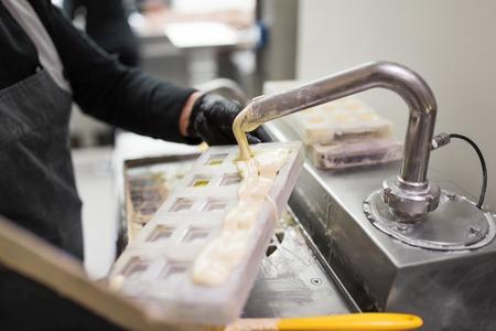 confectioner makes chocolate candies at sweet-shop Foto de archivo - 115613914