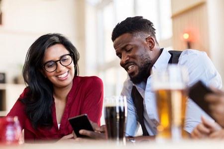 happy man and woman with smartphones at bar
