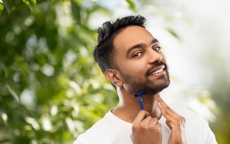 indian man shaving beard with razor blade Stock Photo