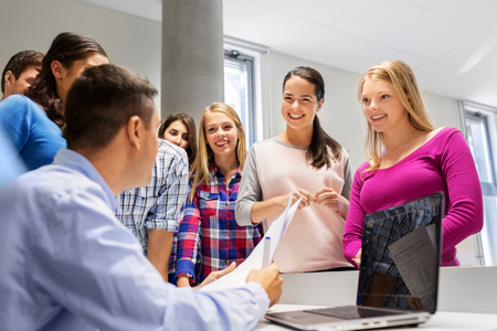students and teacher with papers and laptop Standard-Bild