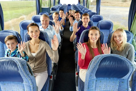 group of happy passengers travelling by bus Banco de Imagens