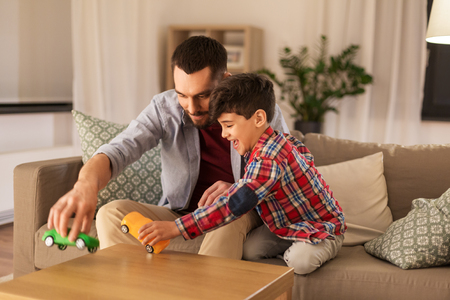 father and son playing with toy cars at home Stock Photo