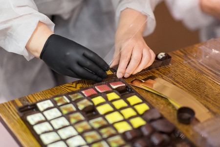 worker packing candies at confectionery shop