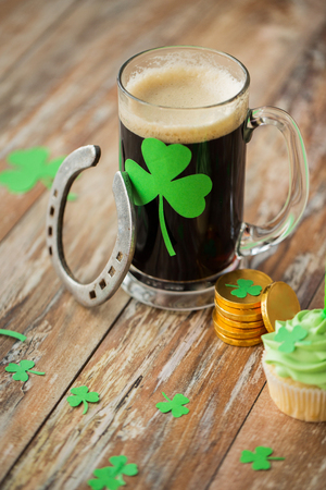 shamrock on glass of beer, horseshoe and coins