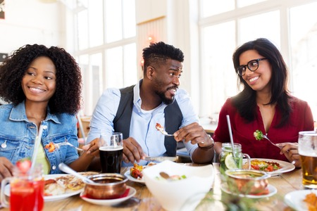 happy friends eating and talking at restaurant Stock Photo