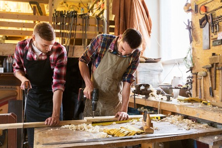 carpenters working with wooden board at workshop Stock Photo