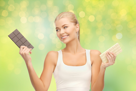 healthy eating, slimming and diet concept - happy woman choosing between dark and white chocolate over summer green lights background