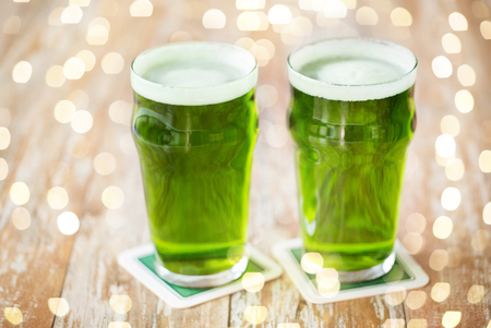 st patricks day, holidays and celebration concept - two glasses of green beer on wooden table Stok Fotoğraf - 115381200
