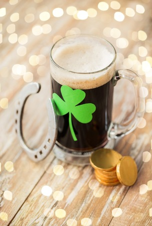 st patricks day, holidays and celebration concept - shamrock on glass of dark draft beer, horseshoe and gold coins on wooden table Stock Photo
