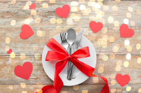 valentines day, table setting and festive dinner concept - plate with spoon, knife and fork tied with red ribbon on wooden background decorated by paper hearts Stockfoto