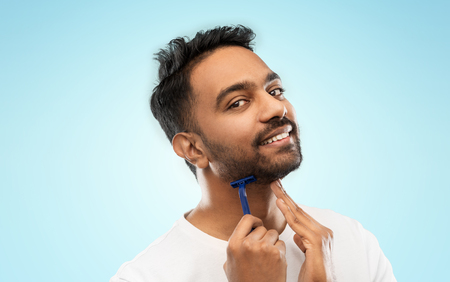 grooming and people concept - smiling indian man shaving beard with manual razor blade over blue background