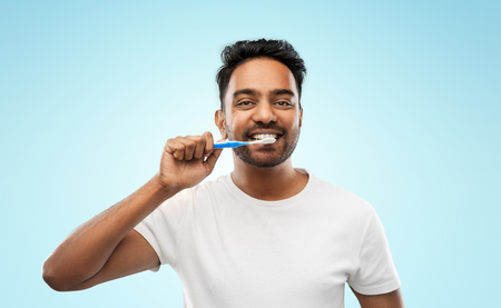 oral care, dental hygiene and people concept - smiling young indian man with toothbrush cleaning teeth over blue background