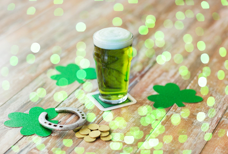 holidays, celebration and st patricks day concept - glass of green beer, horseshoe and gold coins on wooden table
