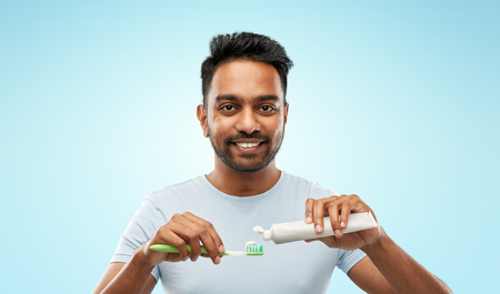 teeth cleaning, dental care and hygiene concept - smiling young indian man with toothbrush and toothpaste over blue background Stock Photo - 115381307