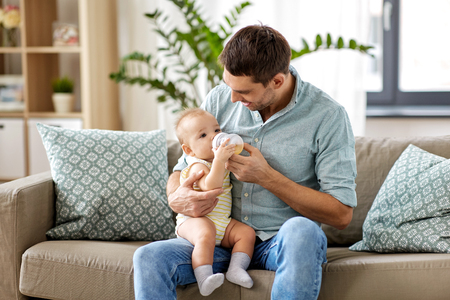 father and baby drinking from bottle at home Banco de Imagens