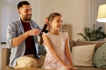 father brushing daughter hair at home