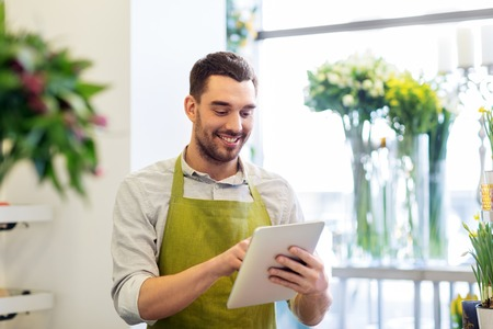 Hombre con tablet pc en la tienda de flores