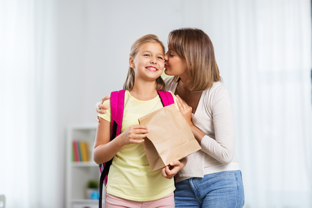 loving mother giving daughter school lunch at home Standard-Bild