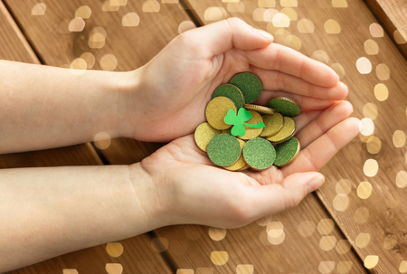 Hands with golden coins and shamrock leaf Stock Photo