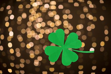 Green paper shamrock over festive lights Stock Photo