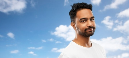 Smiling young indian man over blue sky
