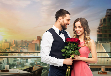 Happy couple with red roses over restaurant lounge
