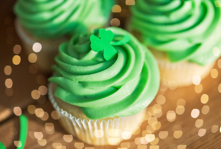 Green cupcakes and shamrock on wooden table Stock Photo