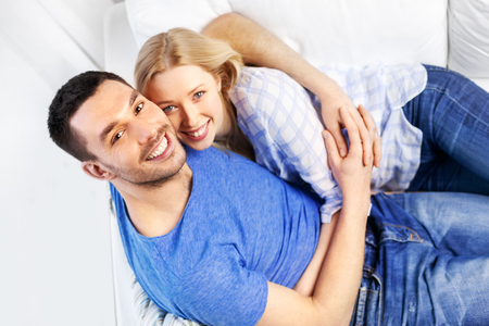 Happy couple sitting on sofa and hugging at home