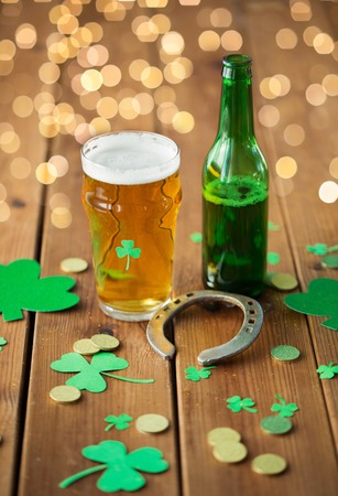 Glass of beer, bottle, horseshoe and gold coins Stock Photo