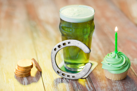 Glass of beer, cupcake, horseshoe and gold coins Stock Photo