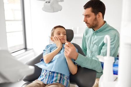 Father supporting son at dental clinic Stock Photo