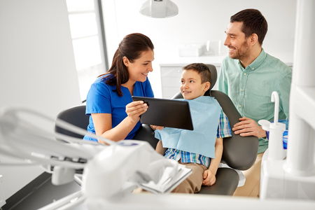 Dentist showing tablet pc to kid at dental clinic