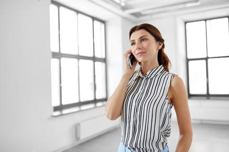 La empresaria llamando al teléfono inteligente en la oficina Foto de archivo