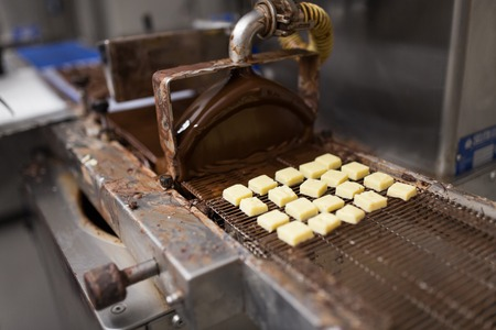 Candies processing by chocolate coating machine Stock Photo