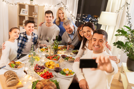 Happy family having dinner party and taking selfie