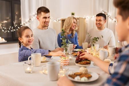 Famille heureuse prenant le thé à la maison