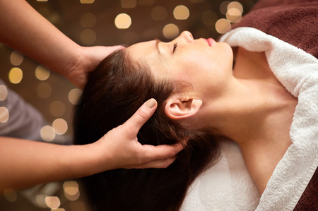 people, beauty, lifestyle and relaxation concept - beautiful young woman lying with closed eyes and having head massage at spa Stock Photo